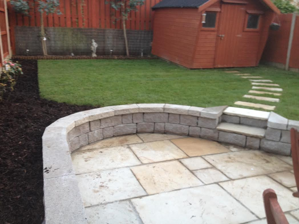 Indian Sandstone paving with retaining wall , roll out turf grass bark mulched plant bed