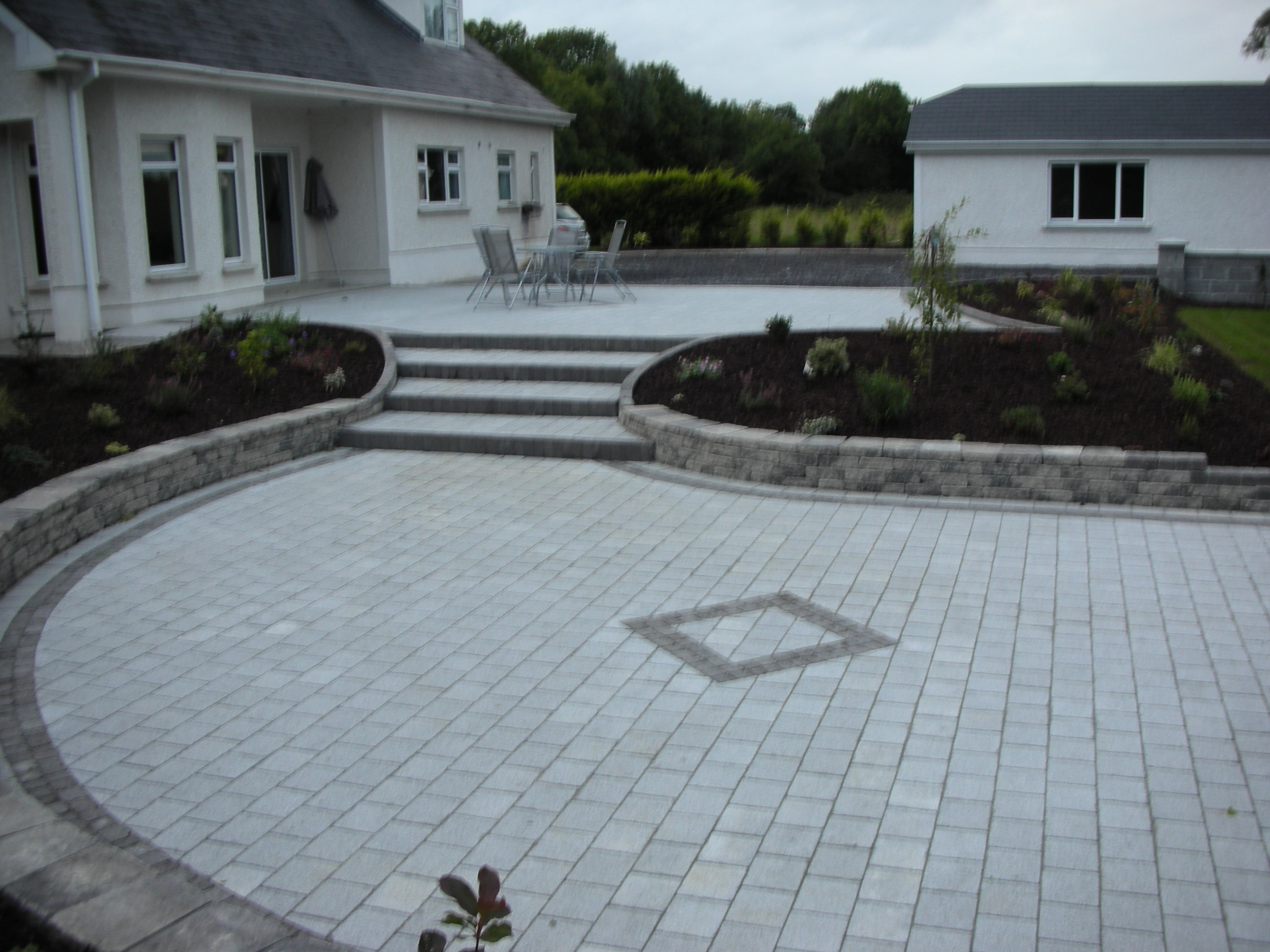 Stepped Paving area incorporating retaining wall to create raised shrub & flower bed.Walling.