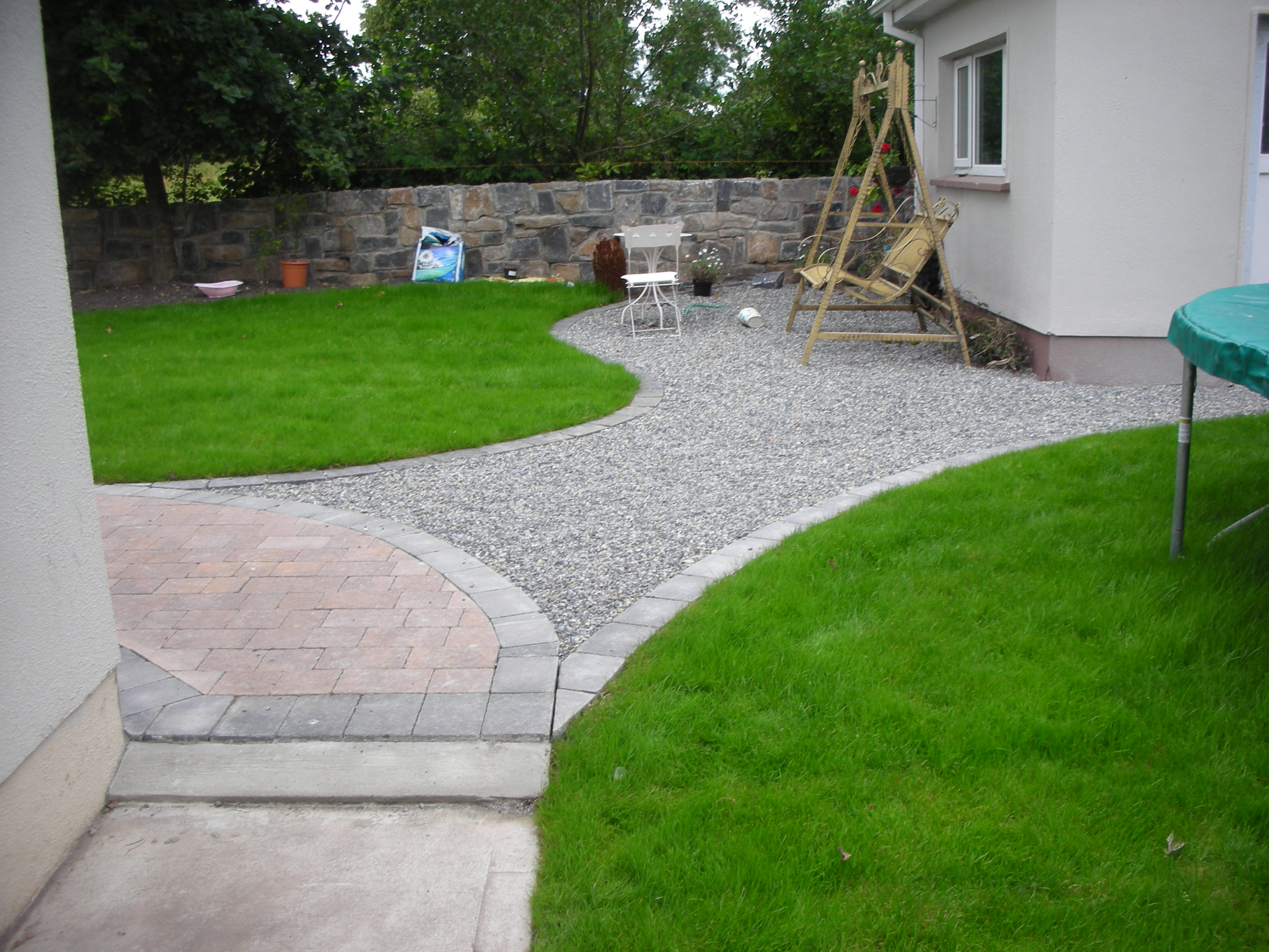 Paving & Roll out lawn with Limestone & Sandstone  mix Stone Wall in background