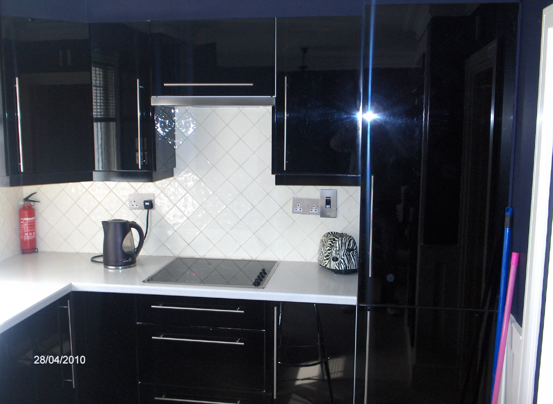 black high gloss kitchen with cream worktop and cream tiles