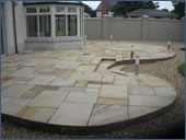 Extension conservatory with sandstone paving.