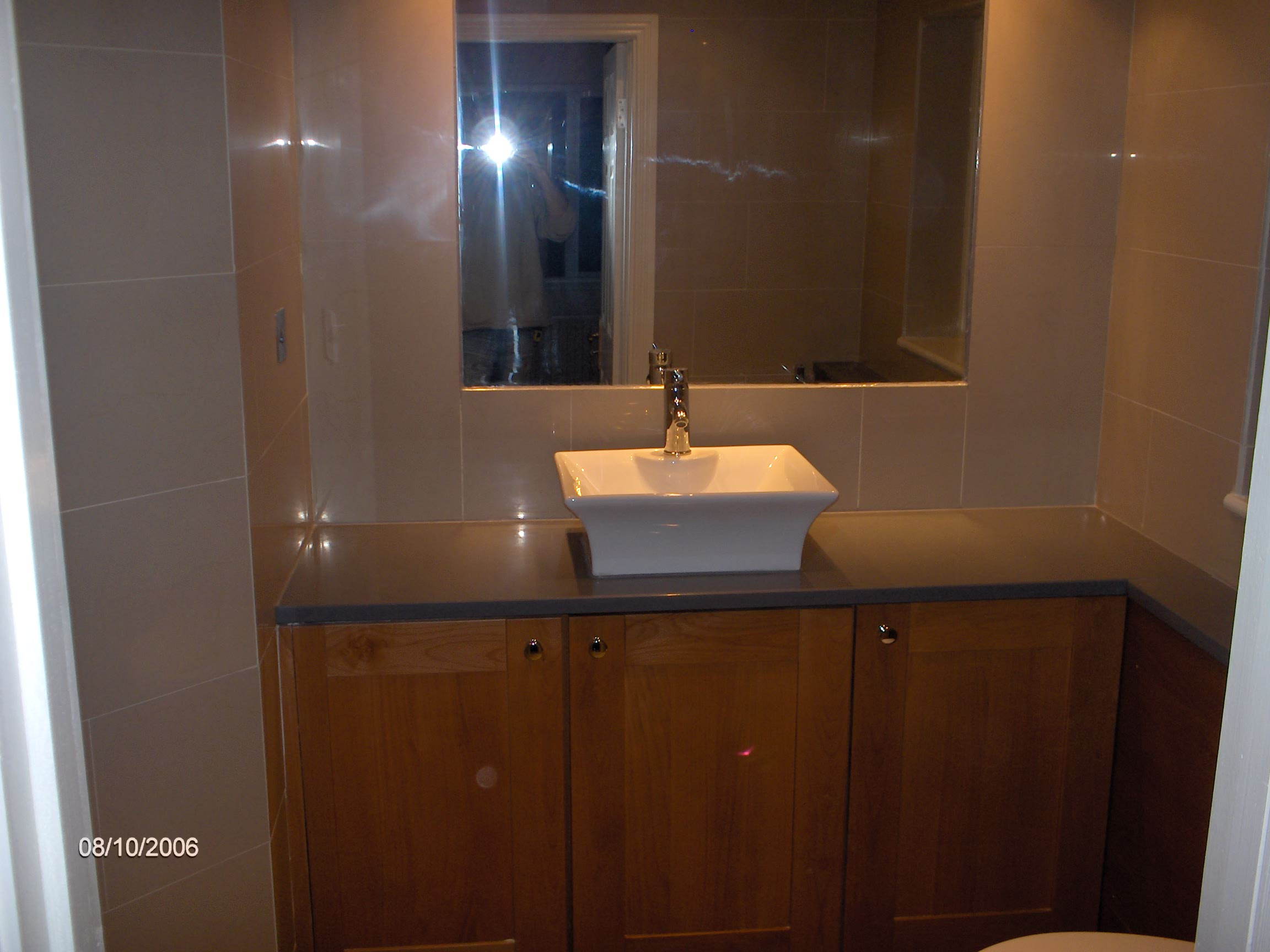 bathroom re-vamp.built in mirror, downlighters, on counter bowl. worktop is man made stone, porcelin wall and floor tiles