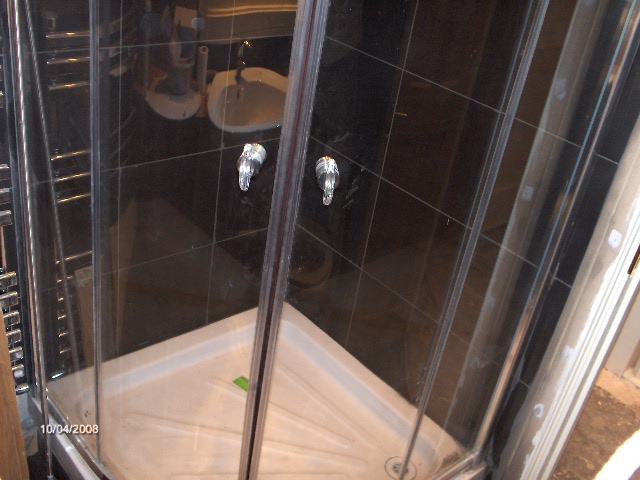 Quadrant shower tray with chrome quadrant doors, triton T 90i electric shower on black porcelin tiles
